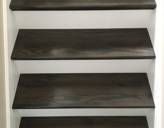 close up of dark hardwood staircase with white background