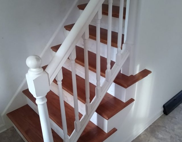 hardwood stair case with white railing